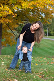 Mother helps baby to walk. Portrait of mother and baby daughter in the park beside trees with Autumn leaves. The mother is holding baby's hands teaching her to Royalty Free Stock Image