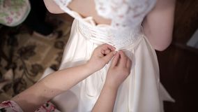 Mother helps the bride to put on a wedding dress. Stock. Hands tie a corset of a wedding dress stock illustration
