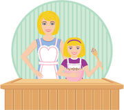 Mother Helps Daughter Bake. A mother helps her daughter bake. Daughter holds bowl with cookie dough Royalty Free Stock Photo