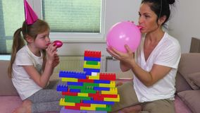 Mother helps daughter blow balloons. In room stock video footage