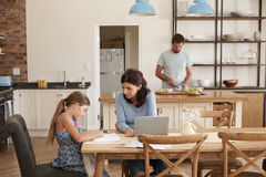 Mother Helps Daughter With Homework As Father Makes Meal royalty free stock photo