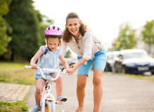 A mother helps her daughter learns to ride a bike Royalty Free Stock Photos