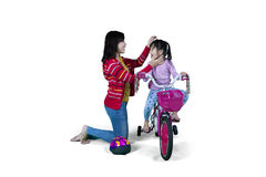 Mother helps her daughter to ride a bicycle Royalty Free Stock Image