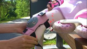 Mother Helps her Daughter to Wear Protective Knee Pads stock video