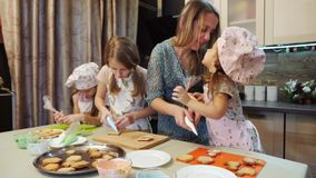 Mother helps her daughters to decorating the cookies with glaze. The girls are dressed in an apron and sheaf cap. Mother and children have fun in the kitchen stock footage