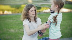 Mother helps his daughter to wear a helmet and protective gear, for roller skating in the park. Woman helps girl put on. Protective knee and elbow pads. Active stock video footage