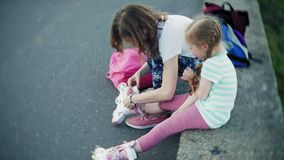 Mother helps his daughter to wear a helmet and protective gear, for roller skating in the park. Woman helps girl put on. Protective knee and elbow pads. Active stock footage