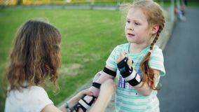 Mother helps his daughter to wear a helmet and protective gear, for roller skating in the park. Woman helps girl put on. Protective knee and elbow pads. Active stock video