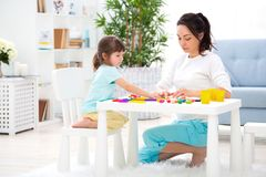 Mother helps a little daughter to sculpt figurines from plasticine. Children`s creativity. Happy family.  stock photo