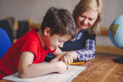 Mother helps son doing homework Stock Photos