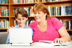 Mother Helps Son Study. Mother (or teacher) helps her young son study on a computer in the library Royalty Free Stock Image