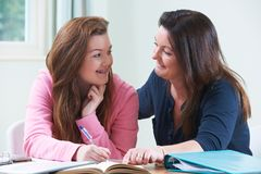 Mother Helping Teenage Daughter With Homework stock photo