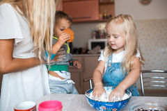 Mother helps to her children to prepare dinner. Mother with family haveing fun at kitchen royalty free stock photography