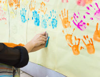 Mother helps the young kid to make a hand print Royalty Free Stock Image