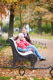 Mother and her adorable daughter on a bench Royalty Free Stock Image