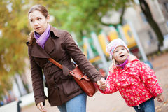 Mother and her adorable daughter walking together Stock Images