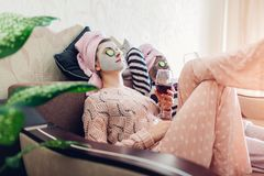 Mother and her adult daughter applied facial masks and cucumbers on eyes. Women chilling while having wine. Sitting on couch at home stock photography