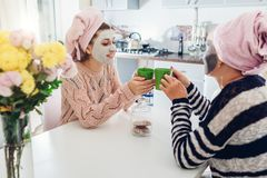 Mother and her adult daughter drinking tea with facial masks applied. Women chilling and talking on kitchen stock image