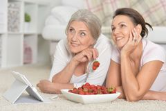Mother and her adult daughter eating fresh strawberries. Mother and her adult daughter looking at tablet while eating fresh strawberries stock image