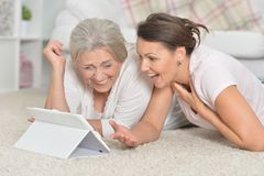 Portrait of mother and her adult daughter lying on floor and looking at tablet stock photography