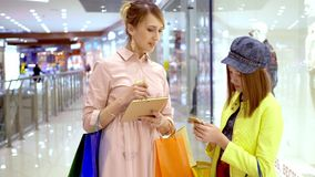 Mother and her adult daughter using tablet computer for planning shopping in mall. stock video footage