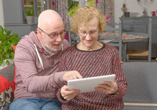 A mother and her adult son looking at a digital tablet Royalty Free Stock Images