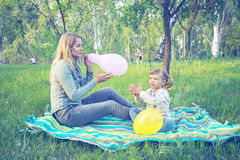 Mother with her amusing daughter inflates colorful balloons in p Royalty Free Stock Photo