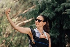Mother with her baby in baby carrier taking selfie with smartphone or blogger stock photo