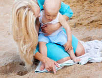 Mother with her baby on the beach. Mother with her baby drawing on the sand Royalty Free Stock Image