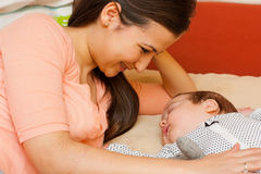 Mother with her baby. Beautiful young mother in bed smiling at her sleeping baby Royalty Free Stock Image