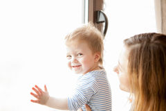 Mother with her baby boy looking at the window Royalty Free Stock Images