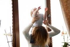 Mother with her baby boy looking at the window Royalty Free Stock Photo