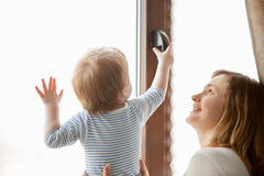 Mother with her baby boy looking at the window Stock Images