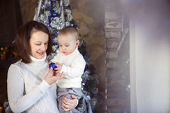 Mother with her baby boy near the Christmas tree Royalty Free Stock Images