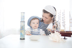 Mother and her baby boy playing with model of ship. Stock Photos