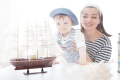 Mother and her baby boy playing with model of ship. Stock Photo