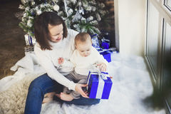 Mother with her baby boy siting near the Christmas tree Royalty Free Stock Image