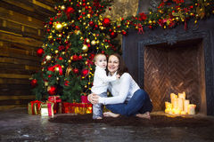 Mother with her baby boy siting near the Christmas tree Royalty Free Stock Photos