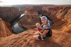 A mother and her baby boy are sitting at the edge of the cliff n stock image