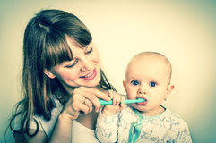 Mother and her baby brushing teeth together - retro style Royalty Free Stock Image