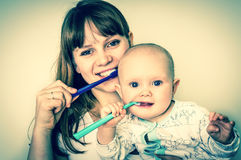 Mother and her baby brushing teeth together - retro style Stock Images