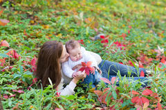Mother and her baby daughter lying among red leaves Stock Photography