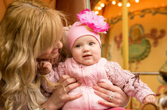 Mother and her baby daughter on merry-go-round Royalty Free Stock Images