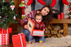 Mother and her baby daughter opening a Christmas gift Stock Photo