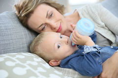 Mother and her baby drinking from baby bottle Royalty Free Stock Photography
