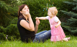 Mother and her baby in garden. Happy mother and her baby in garden Royalty Free Stock Photography