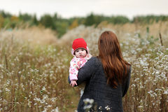 Mother with her baby girl in a meadow. Mother is carryng her little baby girl accross the meadow Stock Images