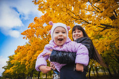 Mother and her baby have fun in the autumn park Stock Photos