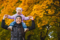 Mother and her baby have fun in the autumn park Stock Image