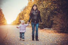 Mother and her baby have fun in the autumn park Stock Images
